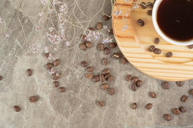 Kaffee auf holzteller mit kaffeebohnen