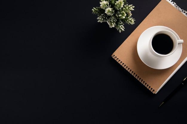 Kaffee auf notizblock mit blume auf schwarzem tisch