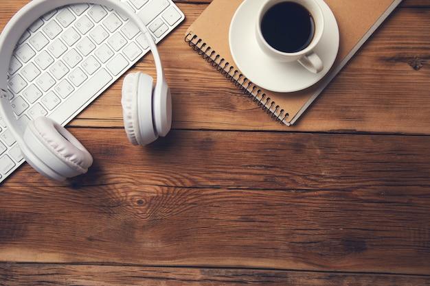 Kaffee auf notizblock mit kopfhörer und tastatur auf tisch