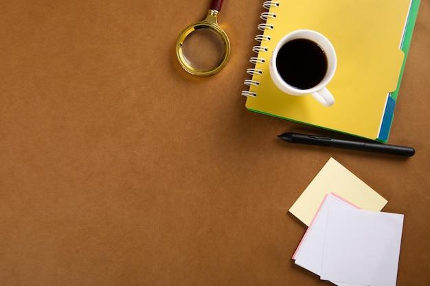 Kaffee auf notizblock mit lupe auf dem tisch