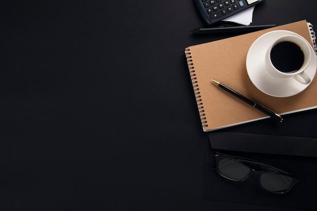 Kaffee auf notizblock mit taschenrechner auf büro schwarz tisch