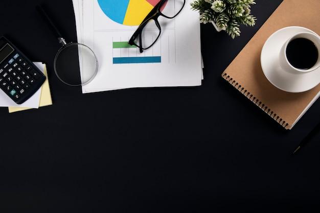 Kaffee auf notizblock mit taschenrechner und grafik auf büroschwarztisch