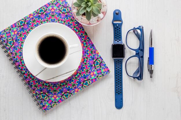 Kaffee auf notizbuch nahe zubehör und anlage