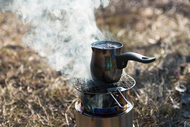 Kaffee auf tragbarem holzbrenner auf campingplatz in den bergen zubereiten