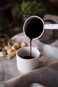 Kaffee aus dem wasserkocher in eine tasse gießen