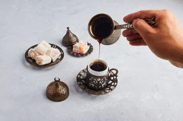 Kaffee aus der kanne in die tasse geben.