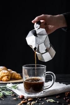 Kaffee aus einem italienischen perkolator gießen, in zurückhaltendem gedreht. männliche hände gießen schwarzen kaffee vom italienischen moka brauer
