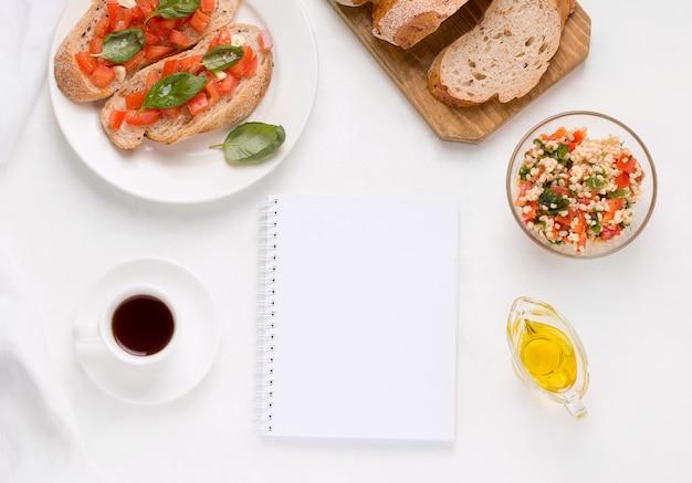 Kaffee, bulgur und tomatensalat, bruschetta-sandwich auf einem weißen tisch. in der nähe befindet sich ein leeres notizbuch für den speicherplatz. veganes gesundes frühstückskonzept