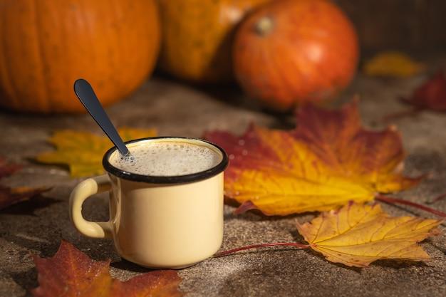 Kaffee-cappuccino in kleiner tasse mit löffel auf herbsthintergrund mit ahornblättern und kürbissen