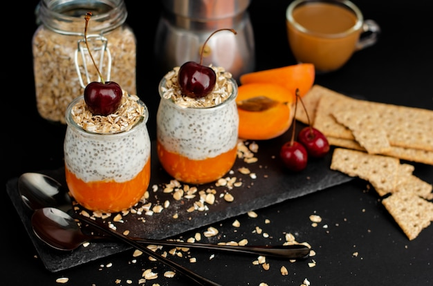 Kaffee, cracker, joghurt-chia-pudding mit frischer aprikose und hafer blättert zum frühstück auf schwarzem ab