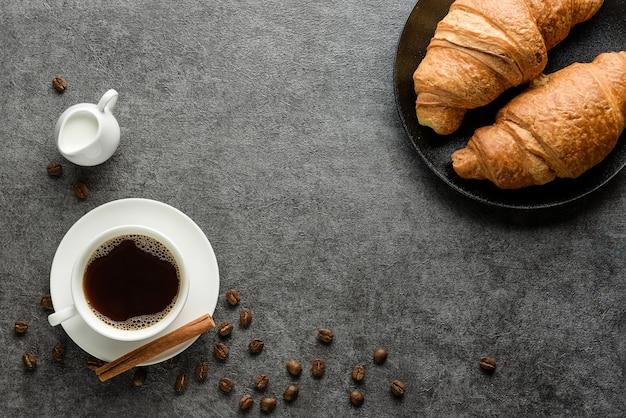 Kaffee, croissants, kaffeebohnen auf strukturiertem hintergrund mit kopierraum. traditionelles frühstückskonzept.
