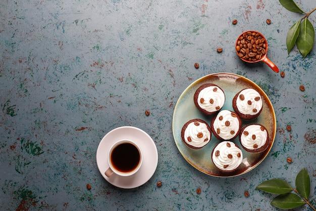 Kaffee cupcakes mit schlagsahne und kaffeebohnen dekoriert.