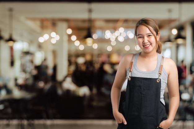 Kaffee der asiatischen jungen frauinhaberin lächelt gerade mit coffee shop