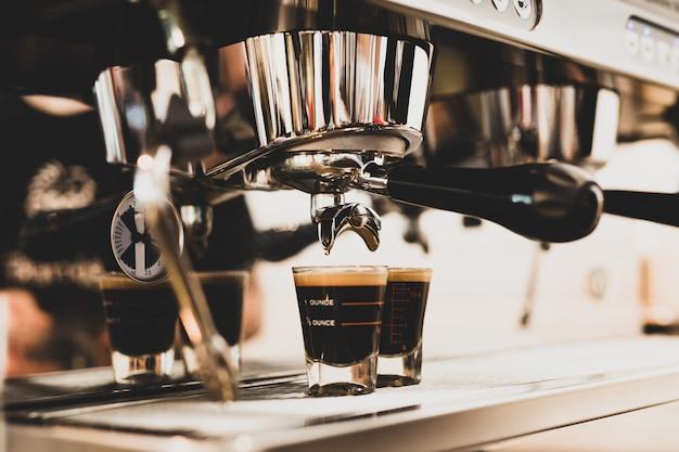Kaffee, der in gläser von der kaffeemaschine im café gießt.