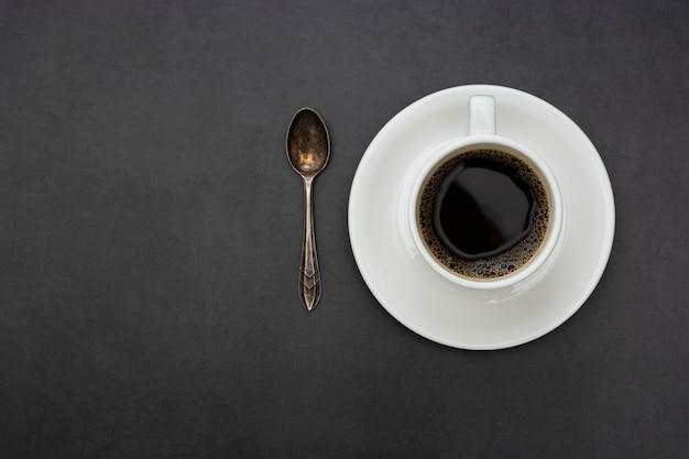 Kaffee. draufsichtlöffel und -platte des weißen tasse kaffees auf dunklem hintergrund