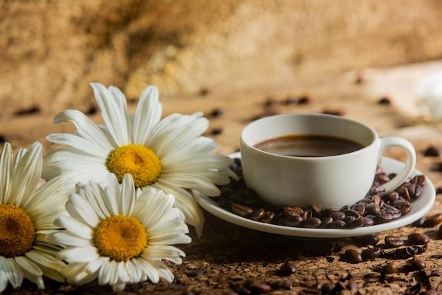 Kaffee. eine tasse kaffee mit körnern auf holz