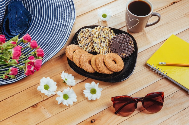 Kaffee espresso steht auf einem holztisch mit keksen, pad und bleistift.