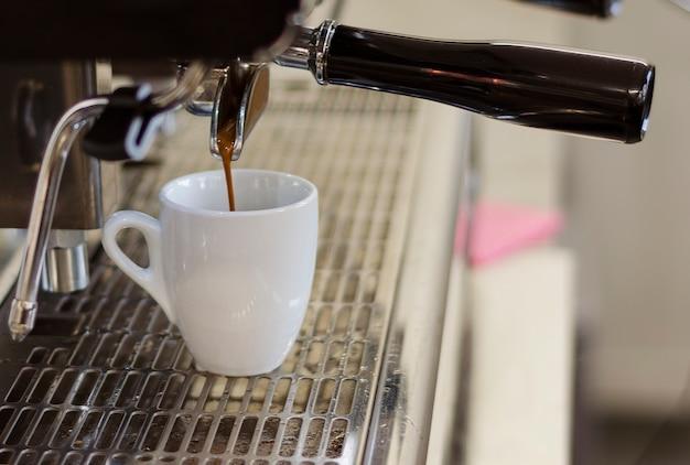 Kaffee fließt von einer kaffeemaschine in eine tasse1