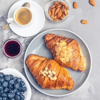 Kaffee, frische croissants, nüsse und beeren.