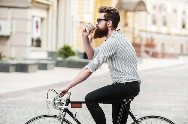 Kaffee für unterwegs. seitenansicht eines jungen bärtigen mannes, der kaffee trinkt, während er draußen auf seinem fahrrad sitzt
