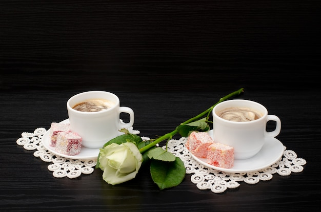 Kaffee für zwei mit orientalischen süßigkeiten, eine weiße rose auf einem schwarzen
