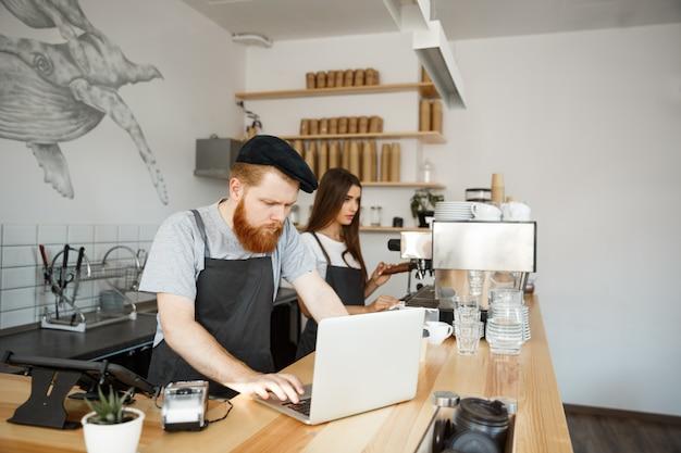 Kaffee-geschäfts-konzept - junger hübscher bärtiger barkeeper, barista oder manager, der im laptop im modernen café arbeitet und plant.