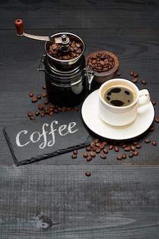 Kaffee handgeschriebene inschrift zeichen auf kreidetafel kaffeemühle und tasse espresso auf dunklem holztisch