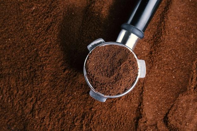 Kaffee-hintergrund. kaffeeautomatik aus der maschine mit gemahlenem kaffee auf kaffeehintergrund. nahansicht.