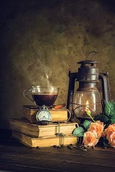 Kaffee im schalenglas auf alten büchern und uhrweinlese mit dem kerosinlampen-öllaternenbrennen