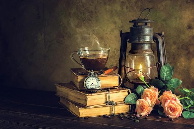 Kaffee im schalenglas auf alten büchern und uhrweinlese mit kerosinlampen-öllaterne