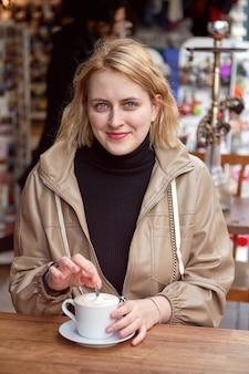 Kaffee im straßencafé für junge lächelnde weiße frau