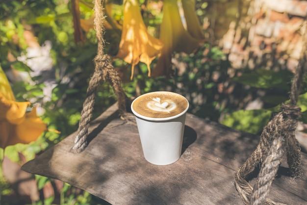 Kaffee im umweltfreundlichen pappbecher im herbstgarten