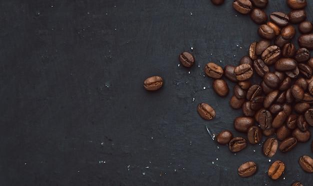 Kaffee in bohnen auf dunklem hintergrund, lebensmittelhintergrund von kaffeekörnern
