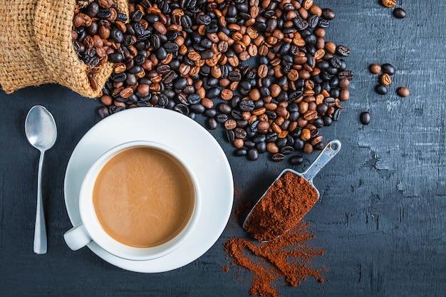 Kaffee in den kaffeetassen und in den röstkaffeebohnen und im gemahlenen kaffeepulver auf dem tisch