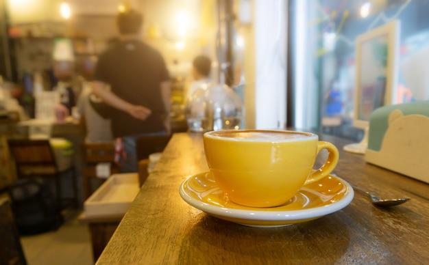 Kaffee in der gelben kaffeetasse und auf einem hölzernen hintergrund