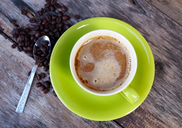 Kaffee in der grünen tasse auf altem holztischhintergrund, draufsicht