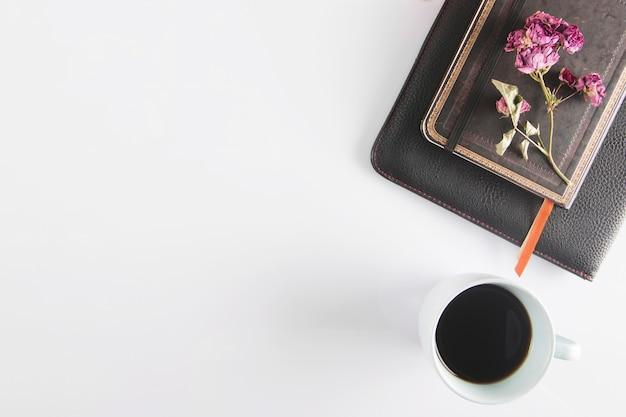 Kaffee in der nähe von notizbüchern und blumen