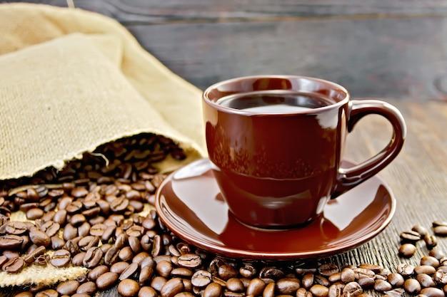 Kaffee in der tasse braun, eine tüte kaffeebohnen auf einem holzbretterhintergrund