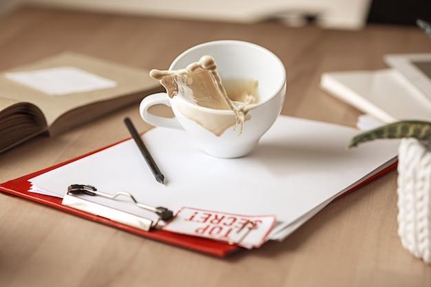 Kaffee in der weißen schale, die morgens auf dem tisch am bürotisch verschüttet wird