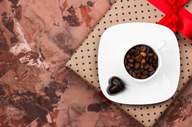 Kaffee in der weißen schale, geschenk mit bürokratie und schokoladen. draufsicht, kopie, raum. essen hintergrund