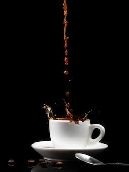 Kaffee in eine weiße tasse mit spritzern gießen