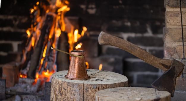 Kaffee in einem türken am offenen feuer kochen. das konzept einer gemütlichen atmosphäre und getränke.