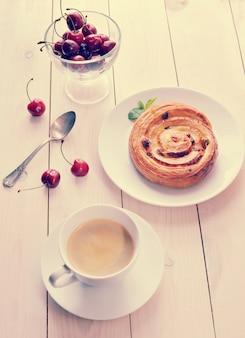 Kaffee in einer tasse, cupcake mit zimtkirschen