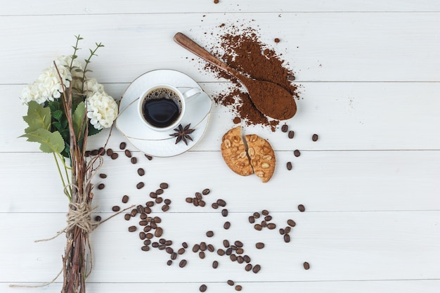 Kaffee in einer tasse mit gemahlenem kaffee, gewürzen, blumen, kaffeebohnen, keksen flach lag auf einem hölzernen hintergrund