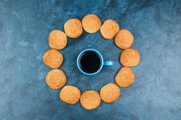 Kaffee in einer tasse mit keksen auf einem dunkelblauen hintergrund