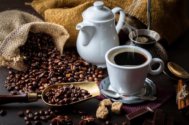 Kaffee in einer tasse und untertasse auf einem schwarzen hintergrund