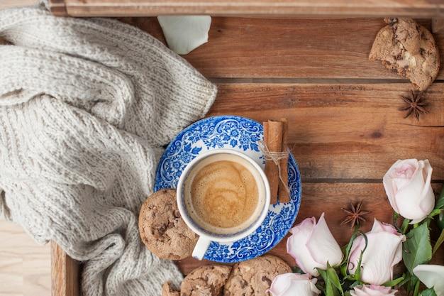Kaffee in einer weinlesetasse auf einem hölzernen hintergrund und einem blumenstrauß von weißen rosen.