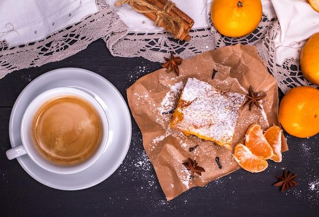 Kaffee in einer weißen runden tasse und einem stück mandarinen-torte