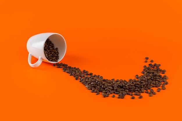 Kaffee in einer weißen tasse auf einem orangefarbenen hintergrund mit kaffeebohnen.