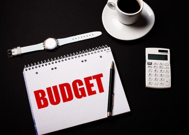 Kaffee in einer weißen tasse, eine armbanduhr und ein taschenrechner auf einem schwarzen tisch. in der nähe befindet sich ein stift und ein notizbuch mit dem text budget